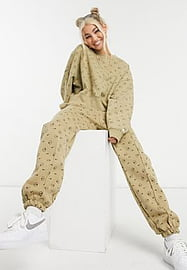 Nike all over logo print joggers in camel-Multi